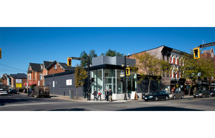 A horizontal panoramic view of the corner of Cannon Street East and James St North, with the Hamilton Artists Inc. building in the center. To the left, there is the Notre Dame House: a large brick building with a red awning. To the right, there are several storefronts extending further down James Street, under a canopy of trees. With its large glass windows and sleek exterior, the Inc. stands out from the surrounding buildings.