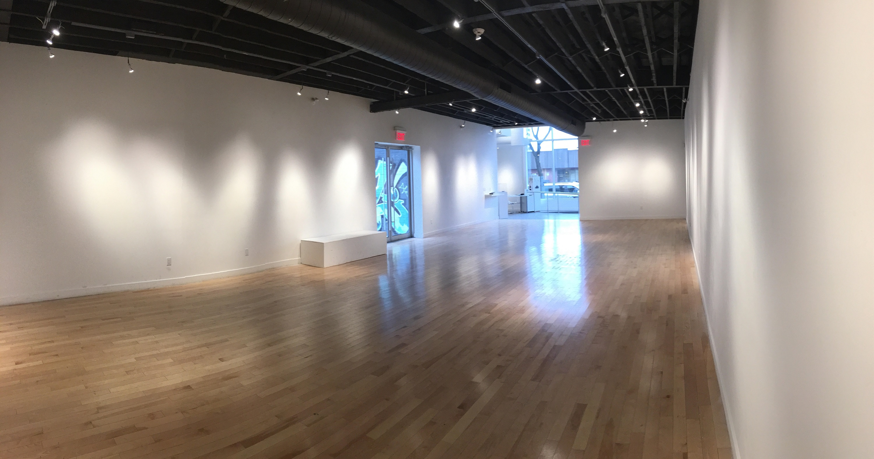 A wide-angle shot of the Cannon Gallery with bare walls. Light bounces off of the laminate floors, especially near the big windows at the front entrance of the building and the glass doorway leading to the courtyard.