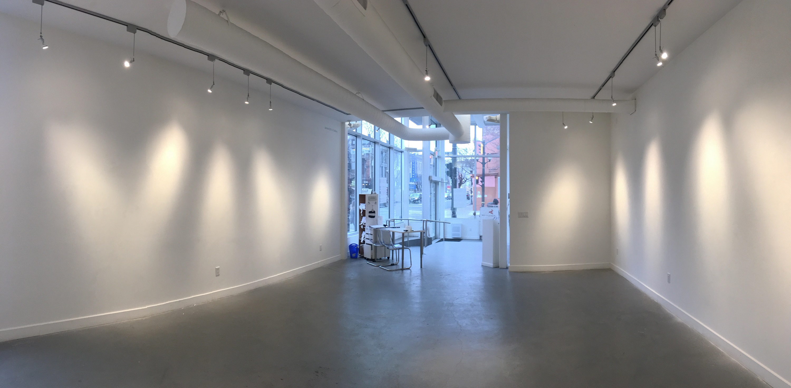 A wide-angle shot of the James Gallery with bare walls. The floor is dark concrete. There are vents and track lighting that run along the ceiling, towards the front entrance. The street corner can be seen through the windows.