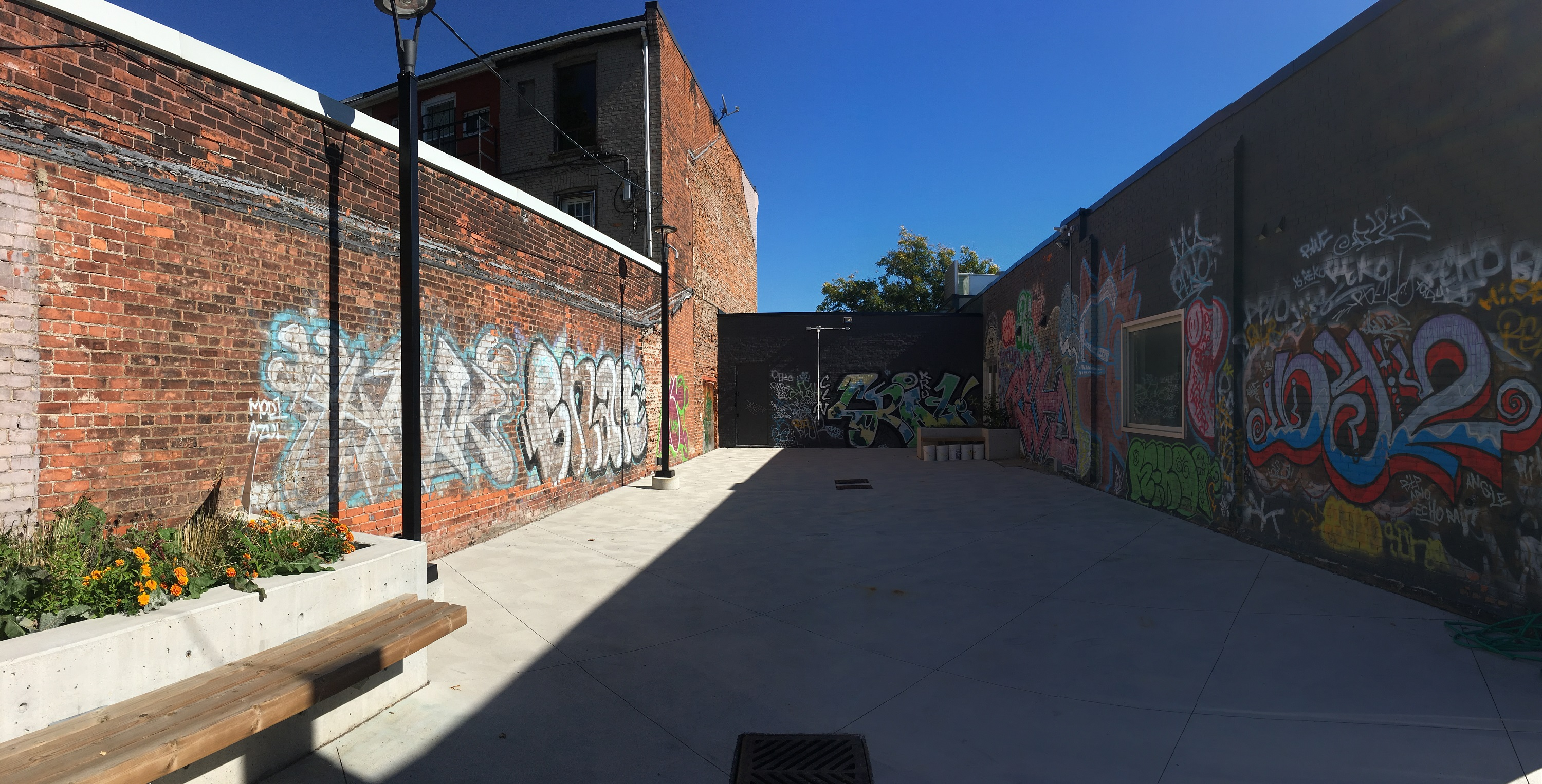 The Inc.'s courtyard, which is enclosed by red brick walls with layers of colourful graffiti on them. To the left, there are concrete flower boxes with wooden benches attached, and to the right is the office window. In the sky above, there is not a single cloud.