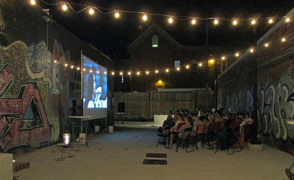 The courtyard at night, lit by strings of warm spherical lights attached to the walls on either side of the space. There is a film being projected, and a small crowd of people seated on folding chairs.