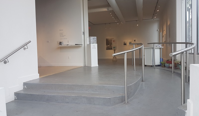 An image of the stairs and ramp directly inside the Inc's front entrance. The ramp is shallow and curved, and has a metal railing on both sides. Both the ramp and stairs lead to the Cannon and James Gallery. The ramp and James gallery have smooth concrete flooring. The Cannon gallery has laminate flooring with end cap molding at the entrance.