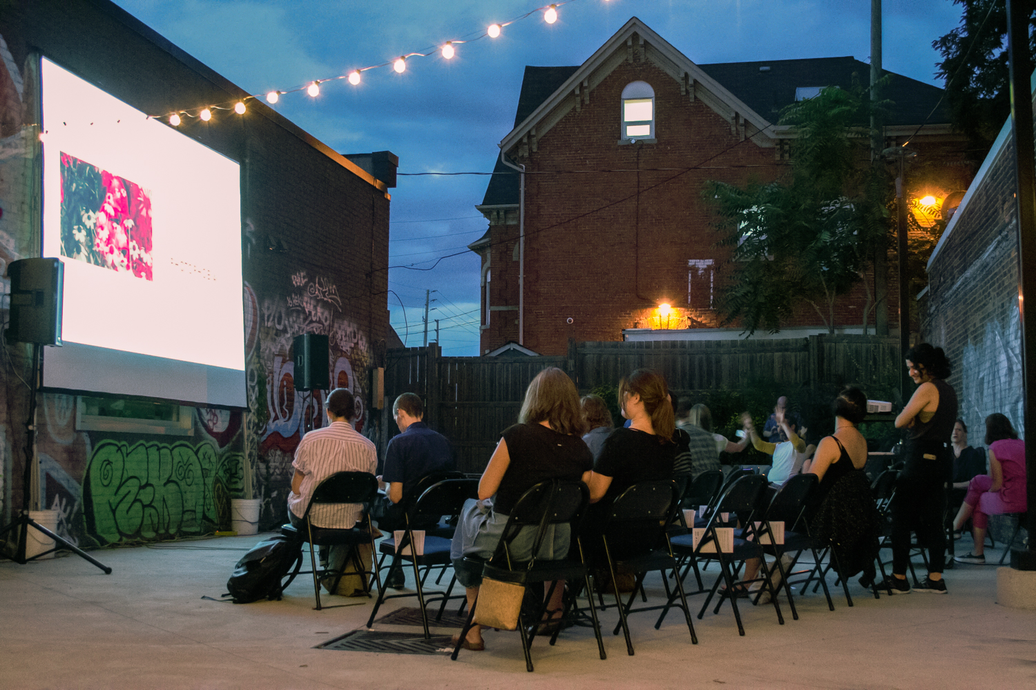 A film is being projected on a screen in the Inc.'s courtyard. The audience is seated in several rows of fold-out chairs; a program is slipped in the side of each unoccupied chair. In the background, a red brick building called the Notre Dame House stands against a dark, overcast sky.