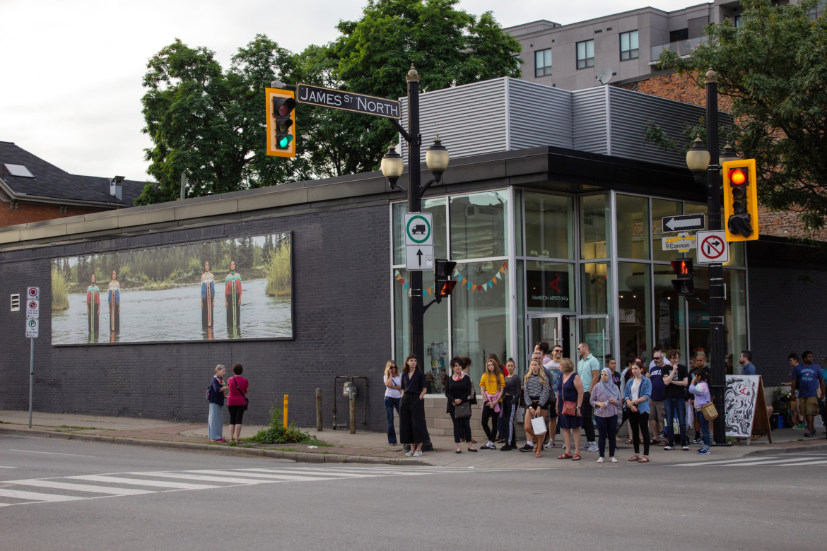 An exterior view of the Inc's building. In the image, Artist Catherine Blackburn's artwork is displayed on a billboard attached to the Cannon Street-facing wall of the Inc. A large group of people are gathered in front of the building.