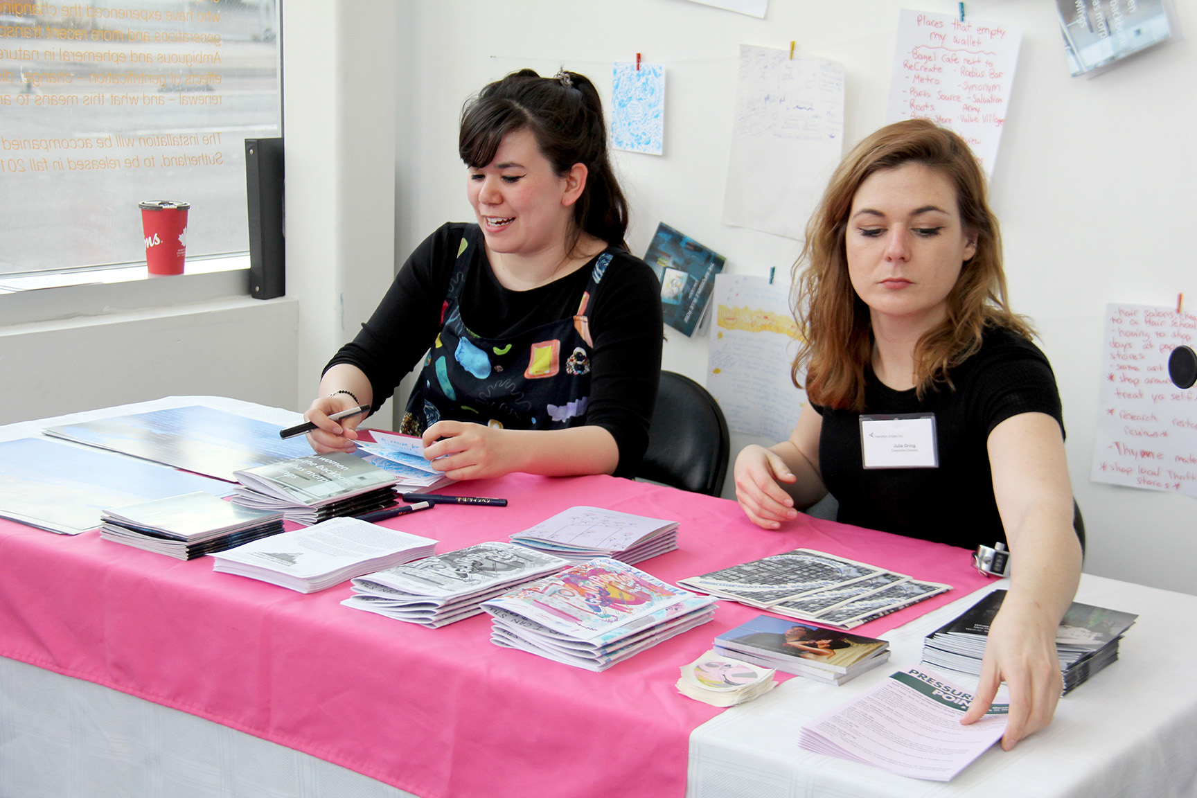 A brightly lit photo of two people seated behind the Zine and Reading corner, which was placed right behind the Inc.'s front door. One person is Julie Dring, a white woman with mid-length wavy hair and winged eyeliner. She is reaching over an assortment of zines and other printed materials on the table in front of her.