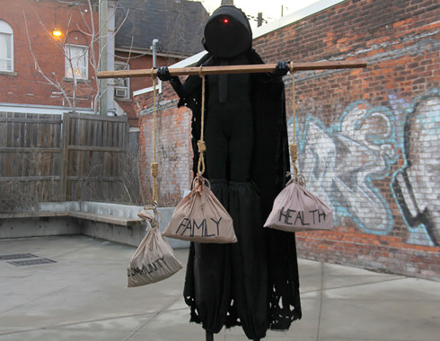 """The hooded figure holding the wooden rod, which has three burlap bags hanging from it. The figure looks as if it is offering them to you. Each bag has a label on it: one says """"community,"""" one says, """"family,"""" and the last says """"health."""" The """"community"""" bag is hanging slightly lower than the others."""