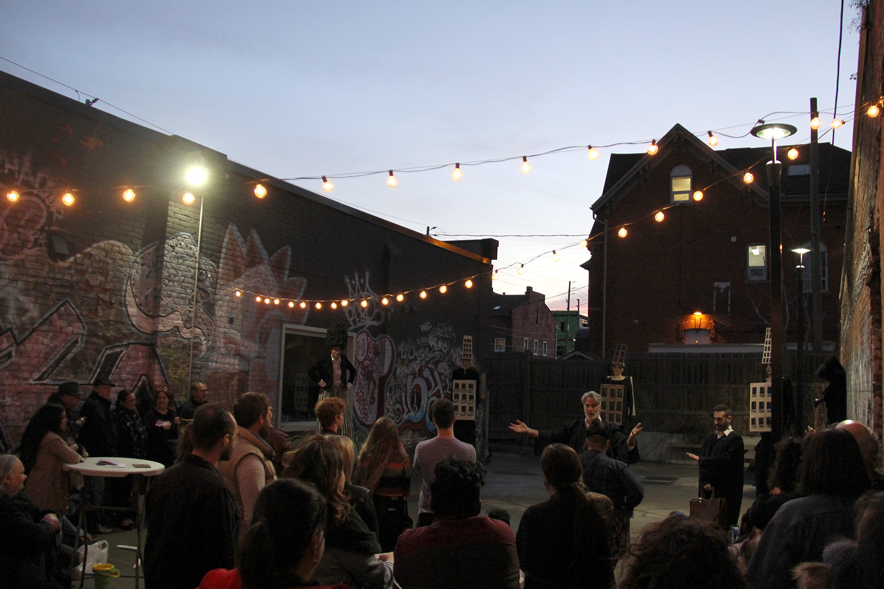 A photo of the Inc.'s courtyard at dusk, framed by the silhouette of the Notre Dame House in the background. There are strings of warm, spherical lights attached to the brick walls on either side of the courtyard. There are 20 or so people seated on fold-out chairs, watching a performance. The performers are dressed in black robes.