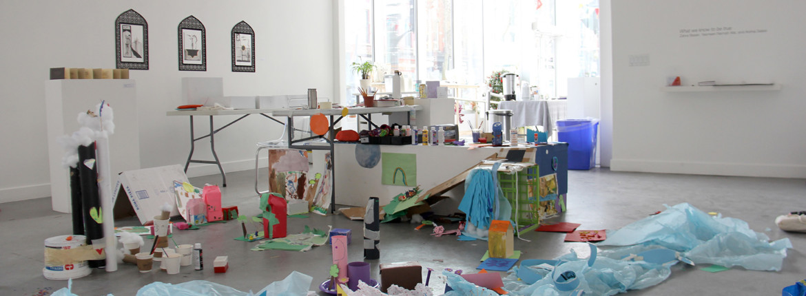 A miniature city constructed in the middle of the James Galley. Part of the city sits on top of a fold-out table and on a long, horizontal white plinth. The other half of the city is on the ground, extending towards a lake that is made out of billowing blue tissue paper. There is a ramp made of cardboard that connects the two parts of the city. The city is made of: a Roma Pizza box, cylinders of paper with cotton balls spilling out the top, a drawing of a rainbow and colourful little houses.