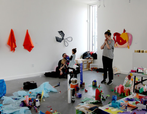 A photo taken from the top of the miniature city. A person in a striped shirt is standing beyond the tissue paper lake. They are smiling with their hands clasped against their chest. There is another adult sitting on the floor with two children.
