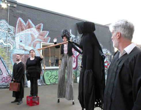 Five performers dressed in black standing in a row in the courtyard. From left to right there is: a person in a black robe holding a briefcase, a person holding one end of a wooden rod with three rope nooses hanging from it, a person standing above with stilts and long striped pants, a hooded figure holding the other end of the rod, and a person with silver hair and a beard.