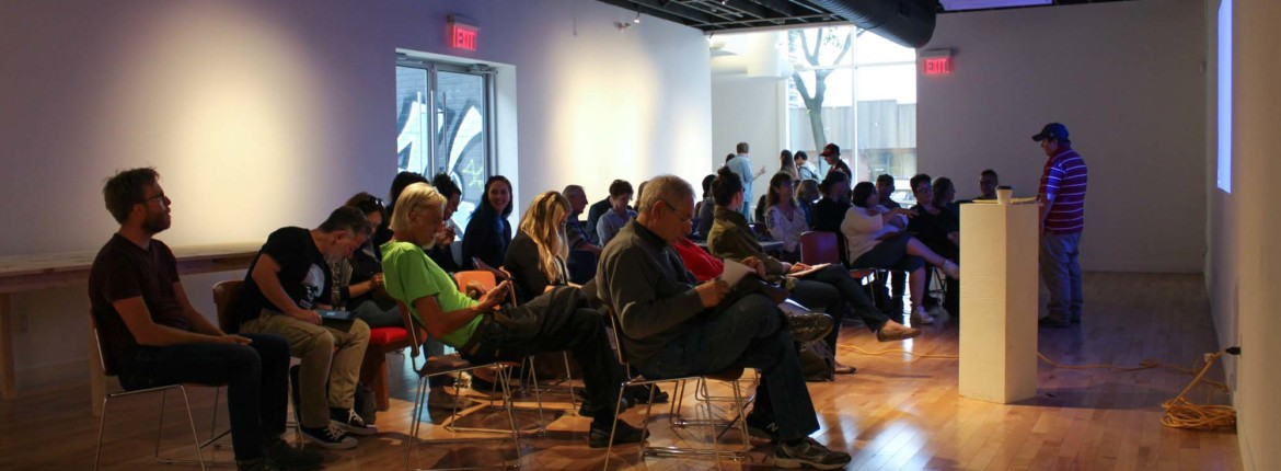 A gathering of people seated in the Cannon Gallery, which is otherwise empty in this photo. There is a presentation being projected on the gallery wall, and a facilitator standing just before it. The facilitator, who appears to be a white man in a baseball cap, is standing beside a tall, narrow plinth with a small disposable cup of coffee sitting on top.
