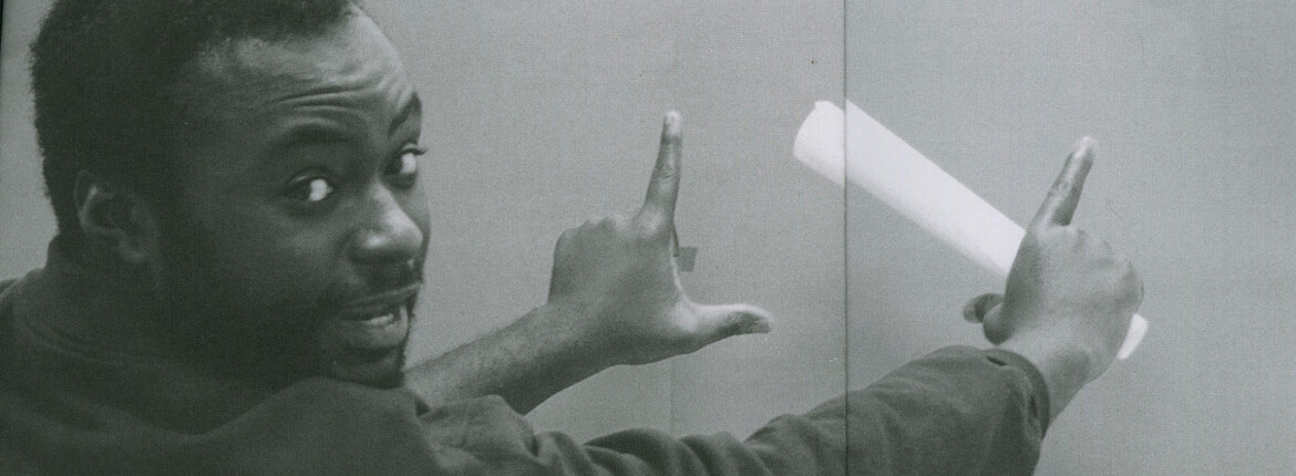 A greyscale, header-style image of Artist Luther Konadu. Konadu is looking over his shoulder at the camera, mid-conversation. He extends his arms, using his fingers to frame something in front of him, as if envisioning an image that has not yet been made.
